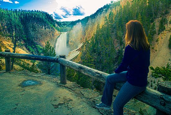 Ragazza che guarda le cascate Lower Falls a Yellowstone